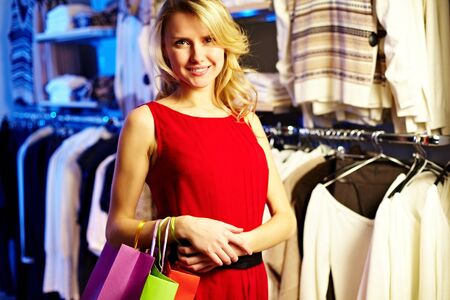 Portrait of pretty woman with paperbags looking at camera in clothing department photo