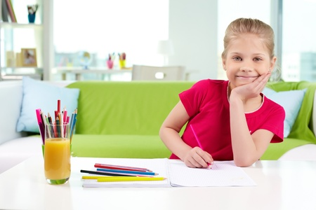 escuela primaria: Retrato de niña encantadora con lápices de colores mirando a la cámara