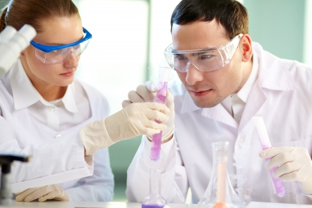 medical attention: Portrait of two chemists holding tubes with pink liquid