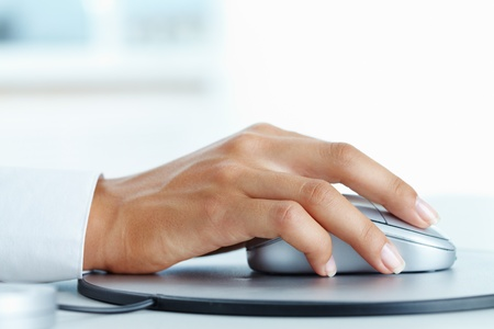 Image of female hand clicking computer mouse photo