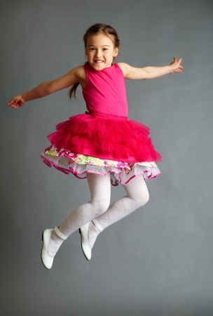 Full length portrait of a cute little girl in jump on grey background Stock Photo
