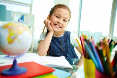 kids artwork: Portrait of lovely girl looking at camera while drawing