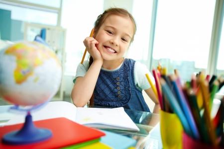 children painting: Retrato de ni�a bonita mirando a la c�mara mientras dibuja