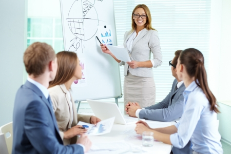 Confident businesswoman explaining something to colleagues at meeting Stock Photo - 13766718