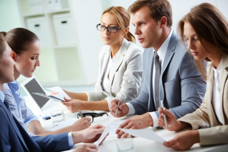 serious woman: Image of confident man explaining something to his colleague at meeting