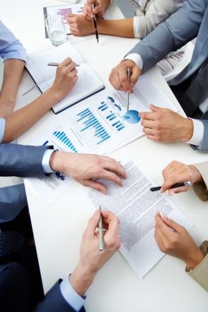 meeting agenda: Image of human hands with pens over business documents at meeting Stock Photo