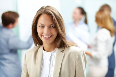 Portrait of pretty business woman looking at camera with working partners on background photo