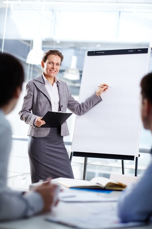 Smart businesswoman standing by whiteboard and explaining her ideas Stock Photo - 13767194