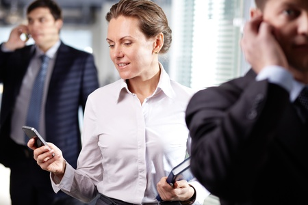 Image of smart businesswoman with cellular phone in working environment