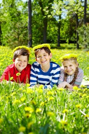 Three children with dandelion wreaths having rest on grass  Stock Photo - 13767262