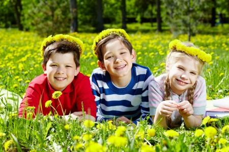 Three children with dandelion wreaths having rest on grass  Stock Photo - 13767264