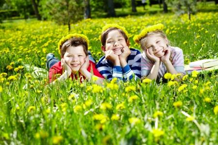 Three children with dandelion wreaths having rest on grass Stock Photo - 13767257