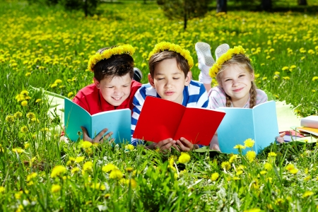 Three friends in dandelion wreaths reading on the lawn Stock Photo - 13767247