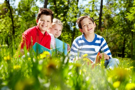 Three friends looking at camera while reading on the lawn Stock Photo - 13767237
