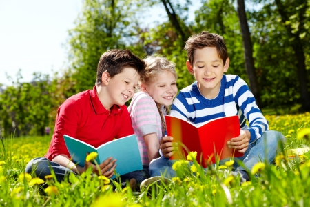 Three happy friends reading on the lawn Stock Photo - 13767240