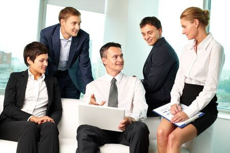 Leader of business team pointing at the screen of his laptop, his colleagues looking at him photo