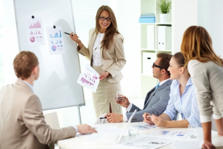 interacting: Confident businesswoman commenting marketing results to colleagues at meeting
