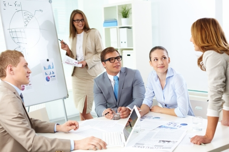 Confident co-workers listening to top manager explanation of her strategy at meeting photo