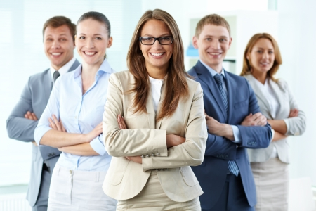 friendly people: Portrait of five businesspeople looking at camera with female leader in front