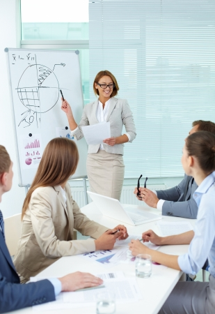 Confident businesswoman explaining something to colleagues at meeting photo