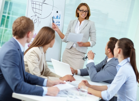 group leader: Confident businesswoman explaining something to colleagues at meeting