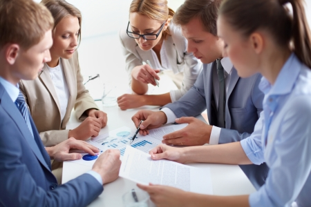 focus group: Image of business partners discussing documents at meeting