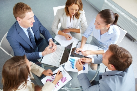 Image of large group of confident partners planning work at meeting photo