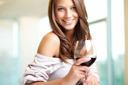 Young beautiful woman with glass of red wine looking at camera  photo