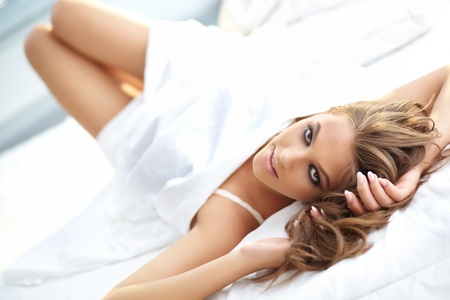 chic woman: Beautiful woman lying in bed and looking at camera