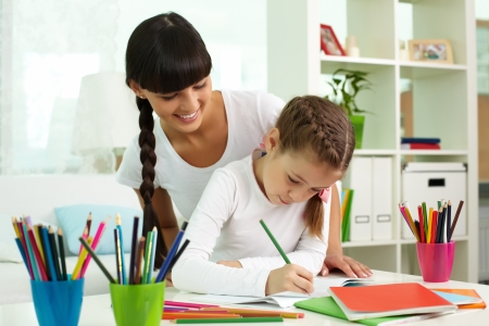 kids artwork: Portrait of cute girl drawing with colorful pencils with her mother near by Stock Photo