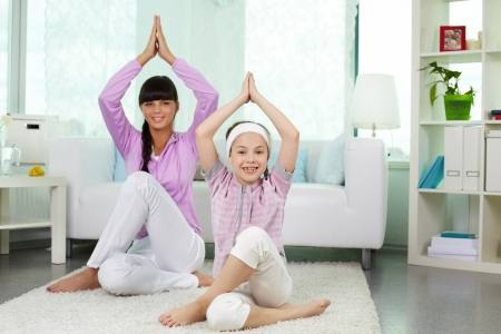 Portrait of little girl and her mother doing yoga exercise at home photo