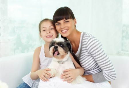 Portrait of happy girl and her mother holding pet and looking at camera with smiles photo