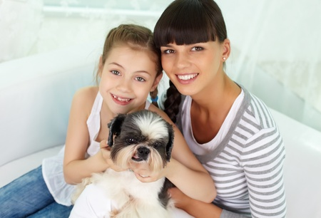 Portrait of happy girl and her mother holding pet and looking at camera photo