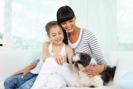 Portrait of happy girl and her mother cuddling shih-tzu dog at home photo