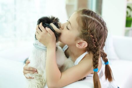 Portrait of happy girl kissing shih-tzu dog at home photo
