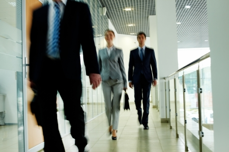 go inside: Businesspeople going along corridor inside office building Stock Photo