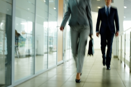 office environment: Businesspeople going along corridor inside office building Stock Photo