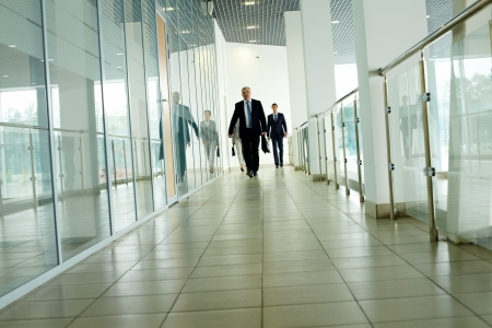 Businesspeople going along corridor inside office building photo