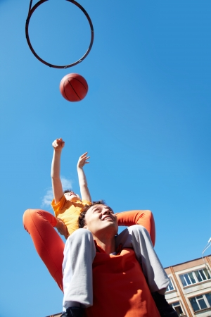 Image of young man and his son playing basketball photo