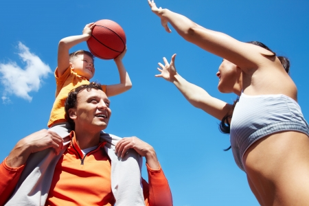 Image of sporty couple and their son playing basketball photo