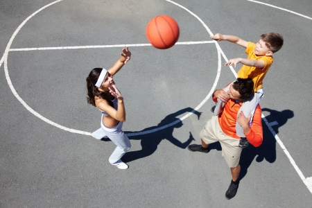 Image of sporty couple and their son playing with ball photo