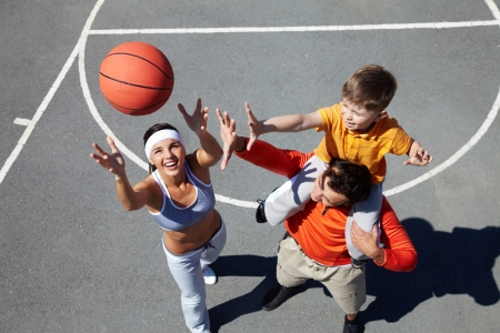 outdoor training: Image of happy female throwing ball with man and kid near by Stock Photo