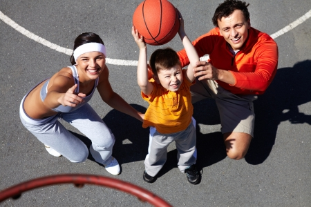 Image of parents showing their son how to throw ball into basket photo