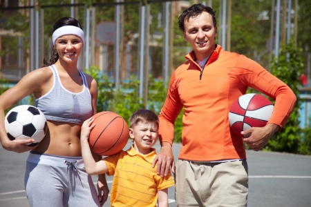 Image of parents and their son holding different balls photo