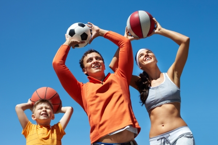 female volleyball: Portrait of happy family throwing balls while playing outside Stock Photo