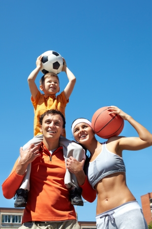 Portrait of happy family holding balls outside photo