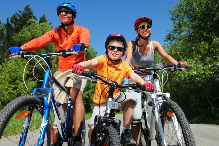 racing bike: Portrait of happy family on bicycles in the park