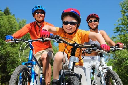 riding helmet: Retrato de ni�o feliz andar en bicicleta en el parque con sus padres detr�s de