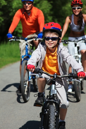 Portrait of happy boy riding bicycle in the park with his parents behind Stock Photo - 13876217