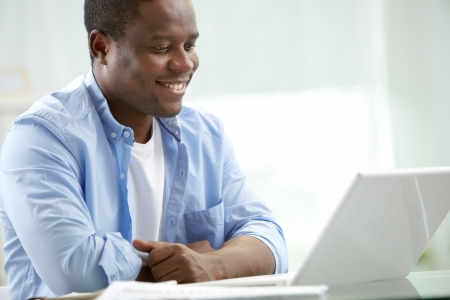 computer learning: Image of young African businessman looking at laptop screen at workplace Stock Photo
